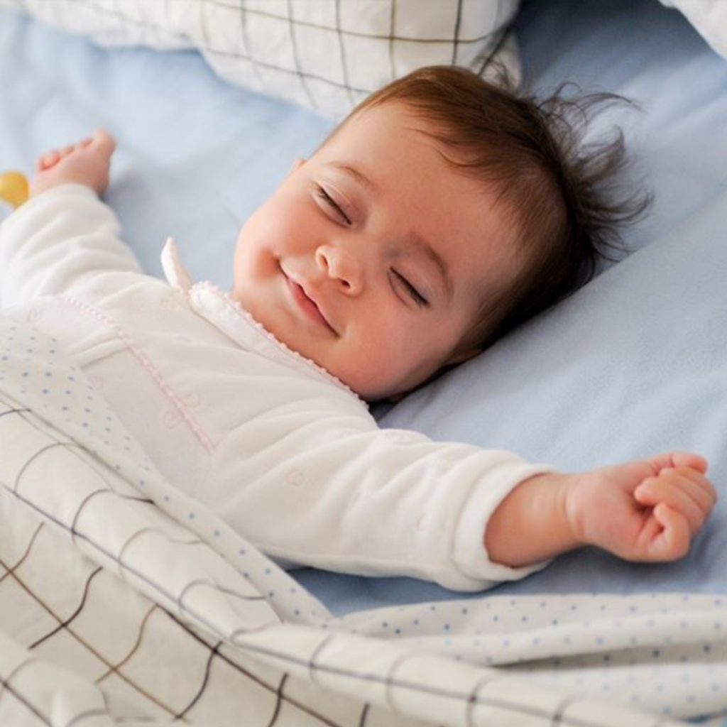 Baby with arms outstretched, eyes closed and smiling lay in a bed